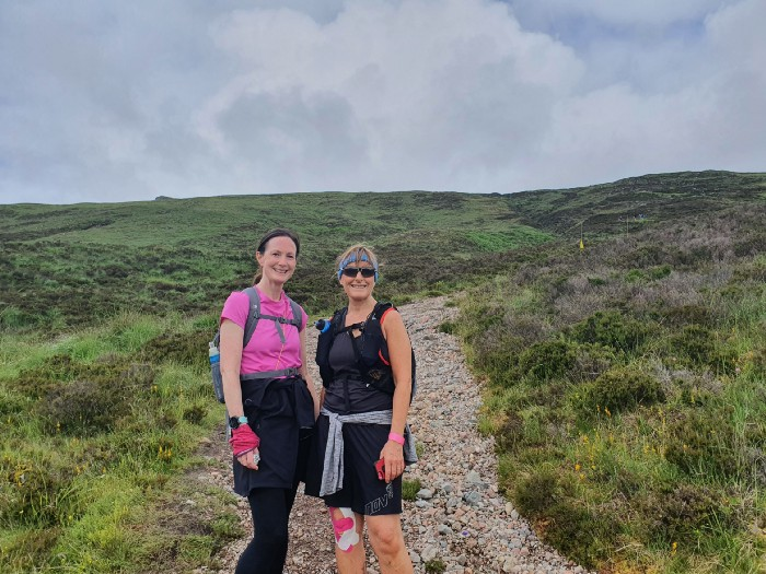2 ladies standing on a mountain path.